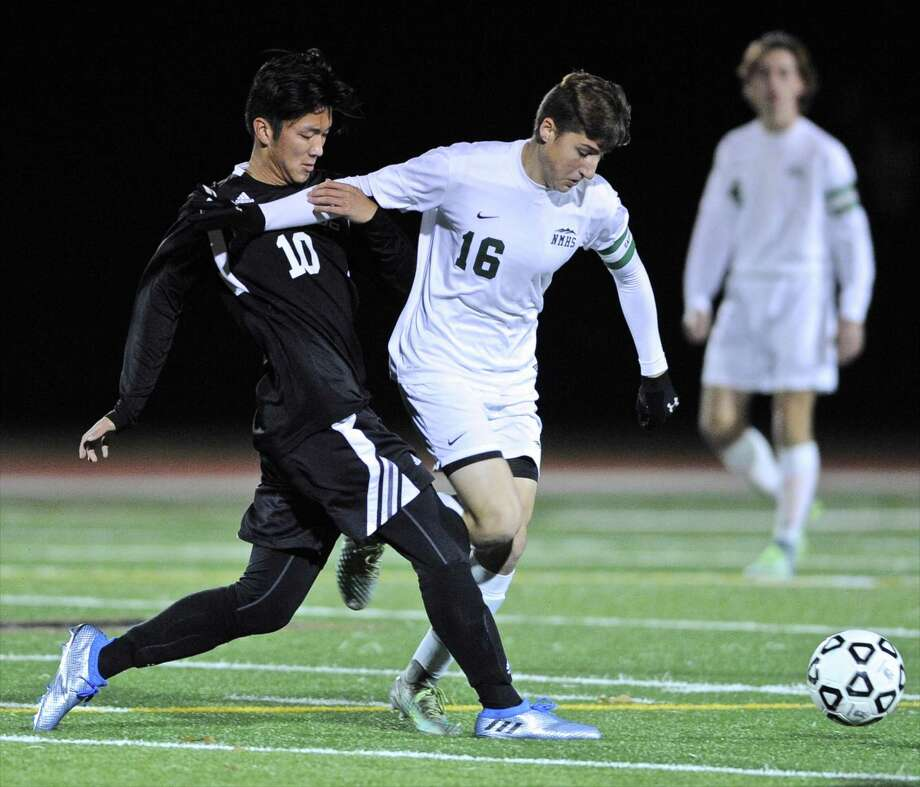 Pomperaug's Austin Wang (10) and New Milford's Matthew Adamou (16) fight for the ball in the SWC boys soccer semi final game between Pomperaug and New Milford high schools, on Tuesday, November 1, 2016, at Joel Barlow High School, Redding, Conn. Photo: H John Voorhees III / Hearst Connecticut Media / The News-Times
