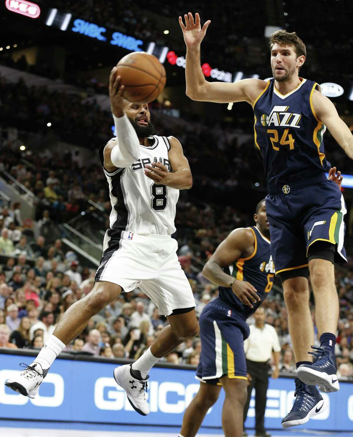 Spurs' Patty Mills makes a pass against Utah Jazz's Jeff Withey (24) at the AT&T Center on Nov. 1, 2016.