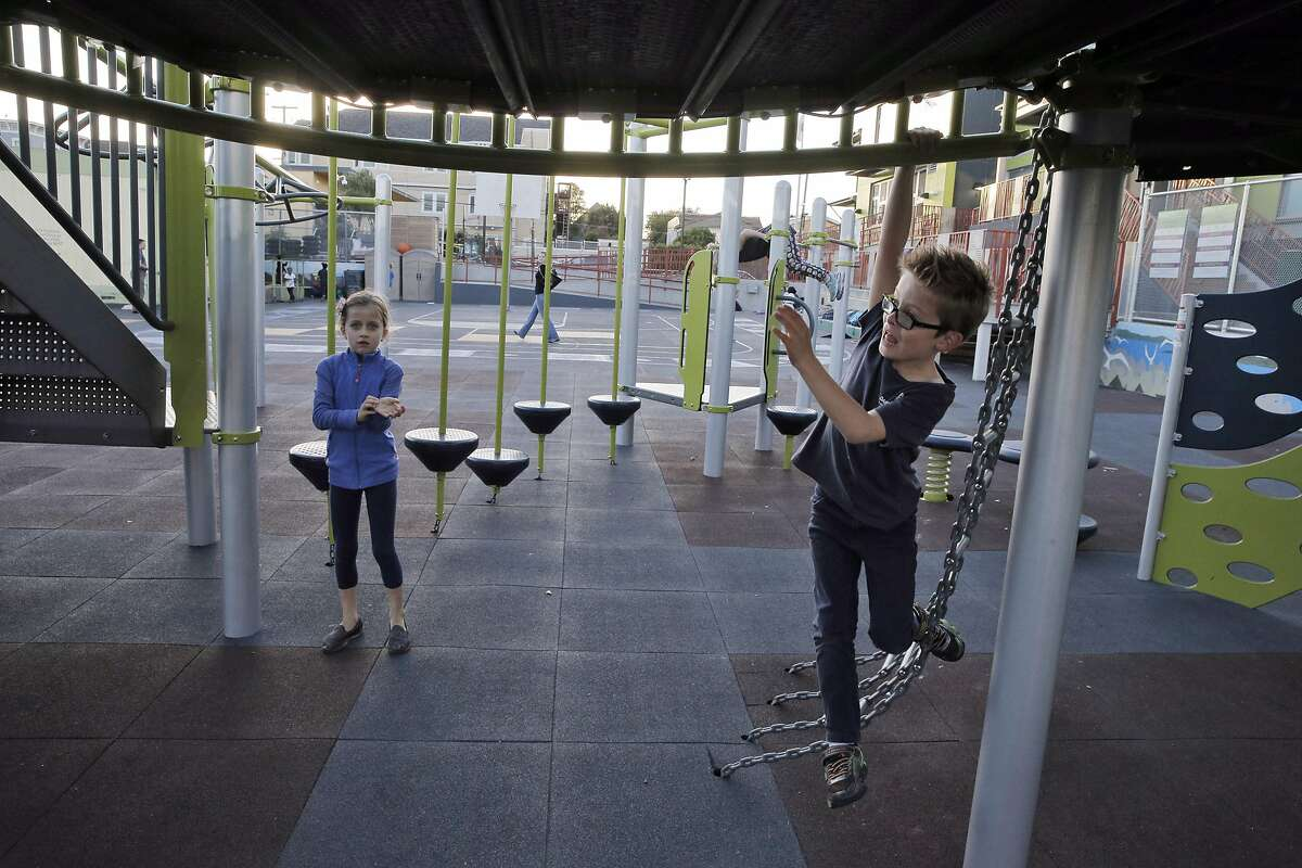 Magdalena Berthiaume, and her brother, Brett, play on the jungle gym as their mother, Erin Loback, attends a PTA meeting at Daniel Webster Elementary in San Francisco, Calif., on Tuesday, October 18, 2016. Parent involvement has helped the school thrive.