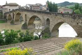 This May 26, 2014 photo shows pilgrims crossing the medieval bridge at Puente la Reina, on Spain's Camino de Santiago. The 500-mile ancient pilgrimage route takes a growing number of pilgrims through many art-filled towns. (Giovanna Dell'Orto via AP)