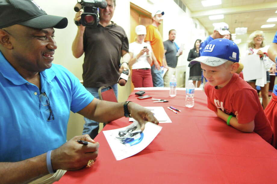 New York Giants great George Martin signs an autograph for life long Giants fan Ayden Swears of Fort Edward, 8, after his father Phil gave blood during the American Red Cross New York Giants Training Camp Blood Drive at the Best Western, on Thursday Aug. 2, 2012 in Albany, NY.  (Philip Kamrass / Times Union) Photo: Philip Kamrass, Albany Times Union / 00018634A