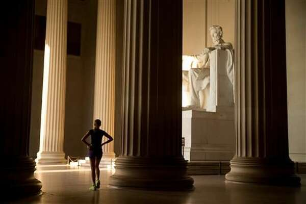 In this May 25, 2016 photo, a runner takes a break and looks around the Lincoln Memorial, in Washington. Fitness buffs around the country are bringing the 'take the stairs' advice to a whole new level as noteworthy landmarks have become unlikely, yet popular new workout sites. (AP Photo/Andrew Harnik)