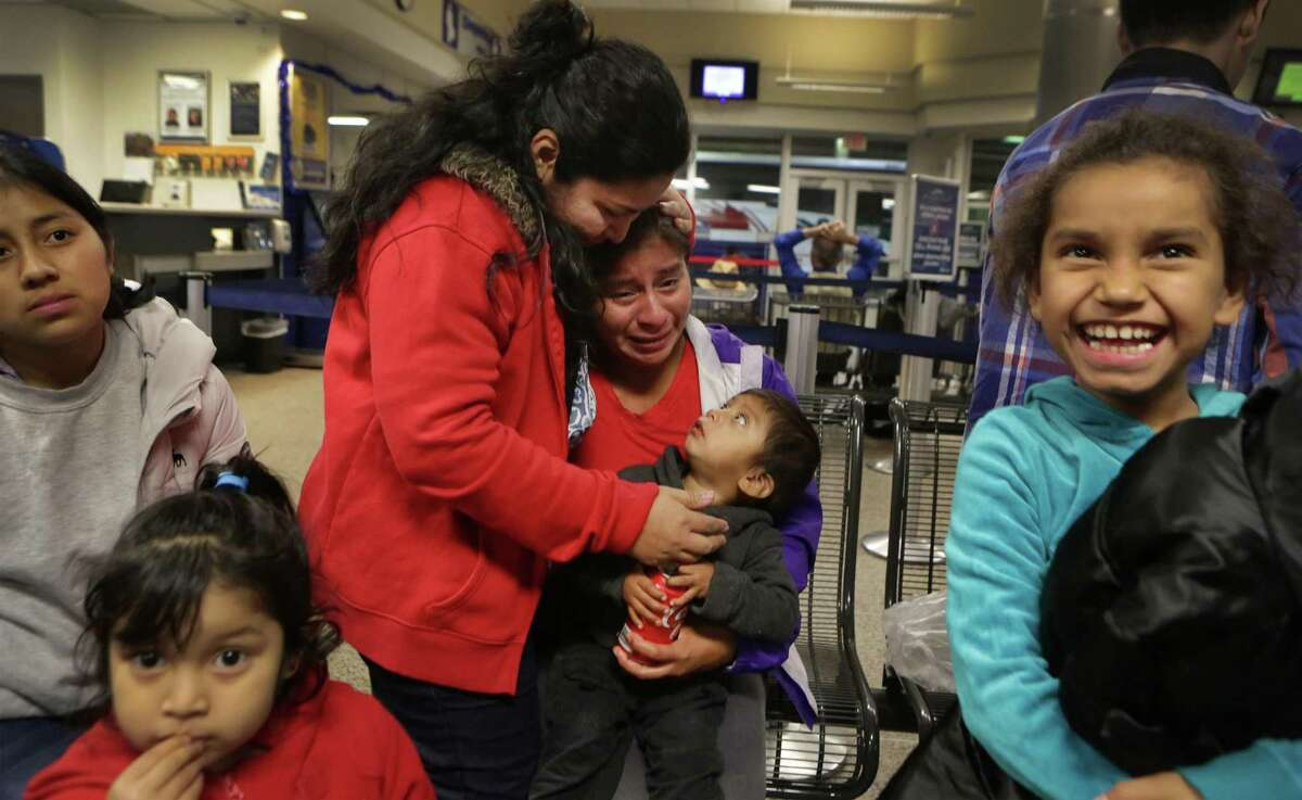 Lisvette Sanches Rodriguez, center, of El Salvador, comforts a grateful Vina Lopez, of Guatemala, with her two year old son, after a group of 11 immigrants from Central America were given food and clothing by members of the Interfaith Welcome Coalition, following their release from the Karnes County Residential Center. The Interfaith Welcome Coalition also found housing for them so they didn't have to spend the night at the San Antonio bus station where they were dropped off without food or money by the Residential Center. At right is Marilin Lopez Figueroa, 8, and at left is Sindy Cotoc Otzoy de Siguin and her 4 year old daughter Heidy. Thursday Dec. 18, 2014.