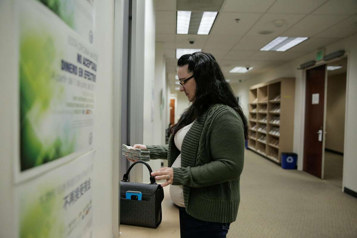 A woman who owns a cannabis delivery service pays her taxes in cash to the Board of Equalization in Oakland, California, on Monday, Oct. 31, 2016. She paid $31,500 in cash.