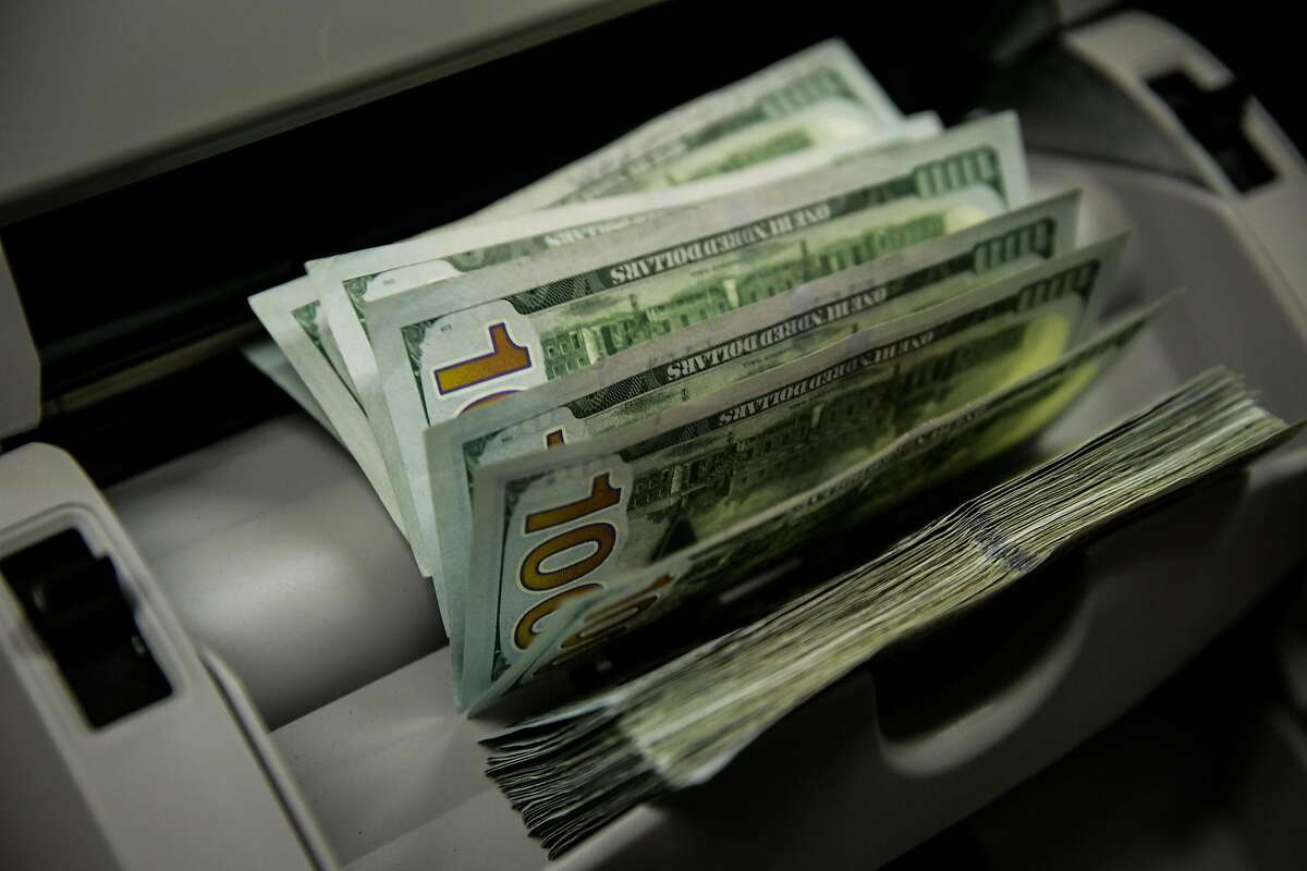 A machine counts and authenticates bills for a woman who is paying her taxes on her cannabis delivery service, at the Board of Equalization in Oakland, California, on Monday, Oct. 31, 2016. She paid $31,500 in cash.
