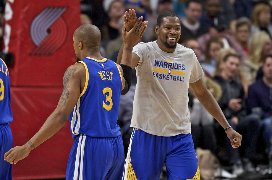 Golden State Warriors forward Kevin Durant, right, high-fives forward David West, left, during the second half of the team's NBA basketball game against the Portland Trail Blazers in Portland, Ore., Tuesday, Nov. 1, 2016. (AP Photo/Craig Mitchelldyer)s Photo: Craig Mitchelldyer, Associated Press
