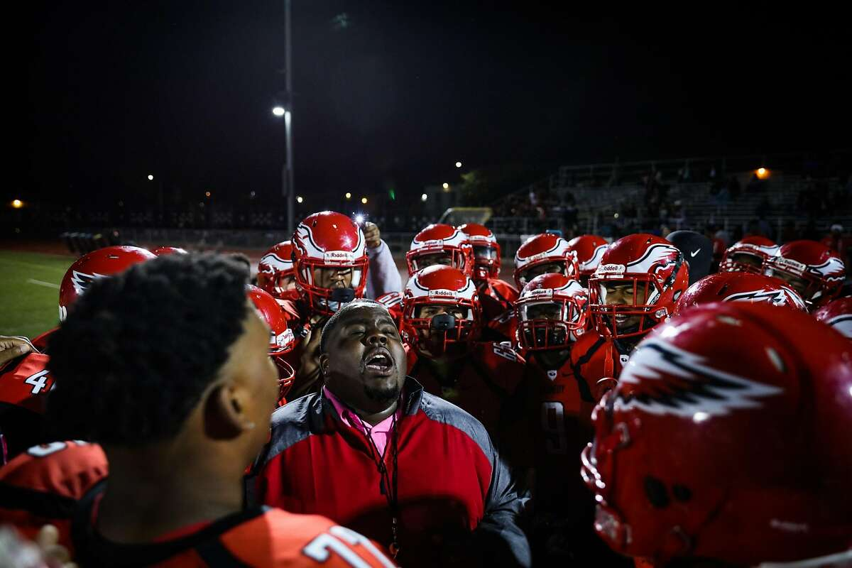 Assistant head football coach Greg Marshall (center) says a prayer with his team, the Eagles, before the start of an important football game, at Kennedy High School, in Richmond, California, on Friday, Oct. 28, 2016.
