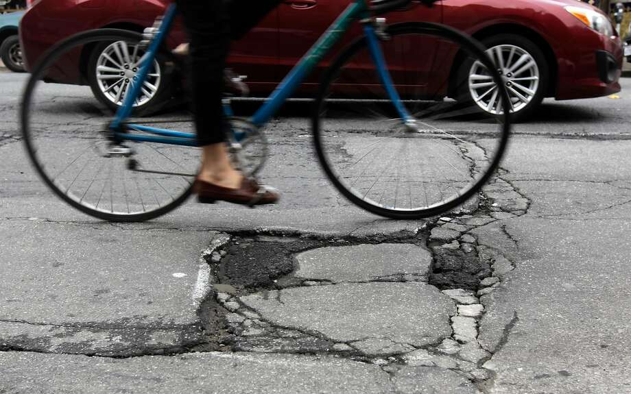 A bicyclist steers clear of a large pothole on Mission Street near Cortland Avenue in San Francisco. on March 5, 2014. The data from 2014 were used in a report released Tuesday that found San Francisco, Oakland and their surrounding neighborhoods had the worst street conditions among the country's large urban areas. Photo: Paul Chinn, The Chronicle