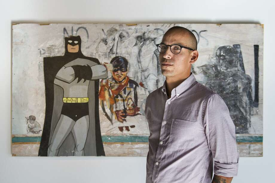 "Artist Andrei Renteria in front of his piece, ""Batman and Robin Do My Dirty Laundry"" at Cinnabar Art Gallery. Cinnabar is staging an exhibit by artists Sarah Fox and Andrei Renteria that opened Thursday. Photo: Alma E. Hernandez / For The Express-News"