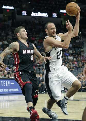 Manu Ginobili makes a no look pass after driving the lane against Tyler Johnson as the Spurs host Miami at the AT&T Center on October 14, 2016. Photo: TOM REEL, STAFF / SAN ANTONIO EXPRESS-NEWS / 2016 SAN ANTONIO EXPRESS-NEWS