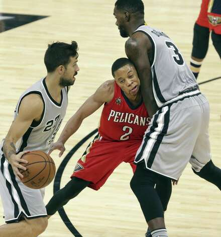 Tim Frazier is pinched in a screen by Dewayne Dedmon for Nico Laprovittola as the Spurs host the Pelicans at the AT&T Center on October 29, 2016. Photo: Tom Reel, Staff / San Antonio Express-News / 2016 SAN ANTONIO EXPRESS-NEWS