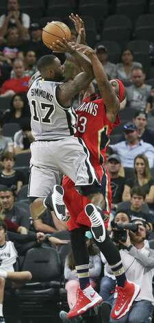 Jonathon Simmons draws the hands of Dante Cunningham into his shot as the Spurs host the Pelicans at the AT&T Center on October 29, 2016. Photo: Tom Reel, Staff / San Antonio Express-News / 2016 SAN ANTONIO EXPRESS-NEWS