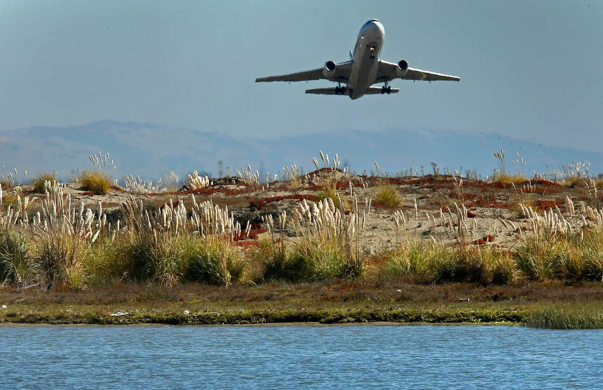 A jet takes off over the original levees that surround Oakland International Airport which opened in1962, as seen on Thurs. Oct 6, 2016, in Oakland, California.