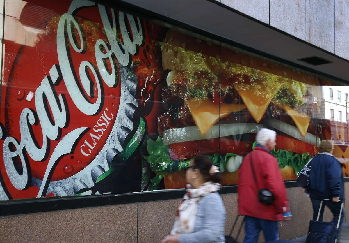 Pedestrians walk past an advertisement for soda outside of a fast food restaurant on Eddy Street in San Francisco, Calif. on Wednesday, Nov. 2, 2016. Supporters and opponents have spent $30 million on Prop. V, the proposed one cent per ounce tax on sugary drinks, more than 23 other local ballot measures combined.