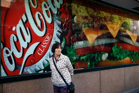 A woman walks past an advertisement for soda outside of a fast food restaurant on Eddy Street in San Francisco, Calif. on Wednesday, Nov. 2, 2016. Supporters and opponents have spent $30 million on Prop. V, the proposed one cent per ounce tax on sugary drinks, more than 23 other local ballot measures combined.