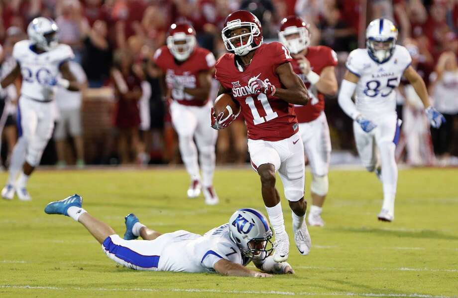 FILE - In this Oct. 29, 2016, file photo, Oklahoma wide receiver Dede Westbrook (11) runs the ball as Kansas cornerback Derrick Neal (7) misses a tackle during an NCAA college football game in Norman, Okla. The Big 12 is a longshot to return to the College Football Playoff this season, and the conference's championship game won't resume until next year.  Still, the Big 12 has to determine a champion to represent the league in a New Year's Six game _ in the Sugar Bowl against an SEC team on Jan. 2 _ and fill the league's six other bowl spots.  (AP Photo/Alonzo Adams, File) Photo: Alonzo Adams, FRE / FR159426 AP
