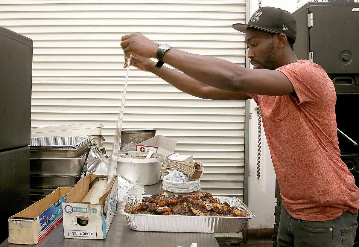 Owner/chef O�Brian Matterson packs Jerk chicken as he fulfills a catering order in the kitchen on Friday, October 27, 2016, in Richmond, Calif.