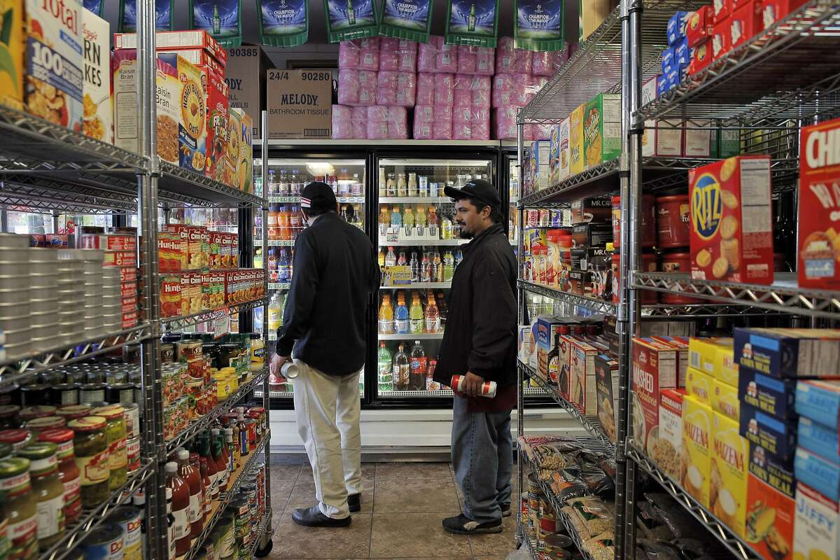 Elias Serrano, left, Francisco Morales, right, look for a soda at US Liquor Beer & Wine store in Berkeley on Monday, August 22, 2016. A new UC-Berkeley study shows that Berkeley's first-of-its-kind-in-the-nation tax on sodas and other sugary drinks has led to a drop in soda consumption in the city's most low-income neighborhoods.