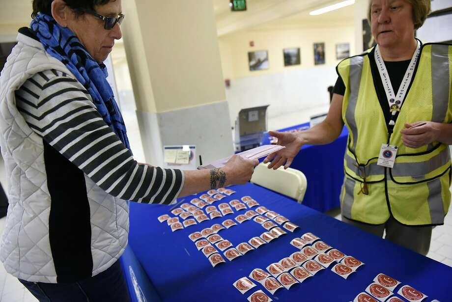 Clair Deem, left, hands an election clerk her mail-in ballot during early voting at City Hall in San Francisco on Nov. 2. Photo: Michael Short, Special To The Chronicle