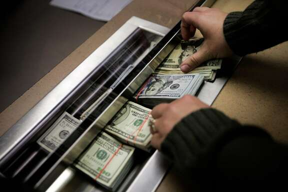 A woman who owns a cannabis delivery service slips her money through a cashier window as she pays her taxes in cash to the Board of Equalization in Oakland, California, on Monday, Oct. 31, 2016. She paid $31,500 in cash.