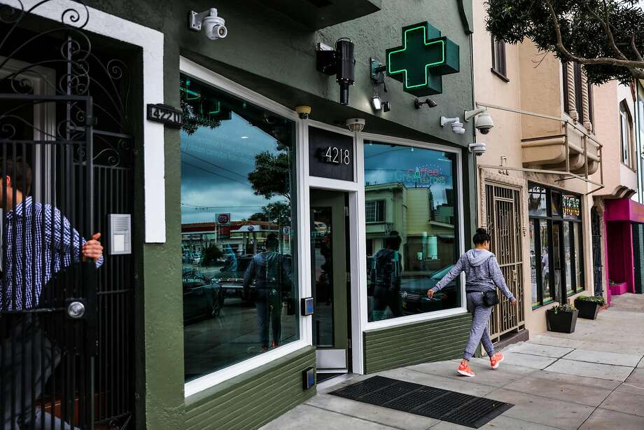 People walk by the exterior of cannabis dispensary The Green Cross in San Francisco. Photo: Gabrielle Lurie, The Chronicle
