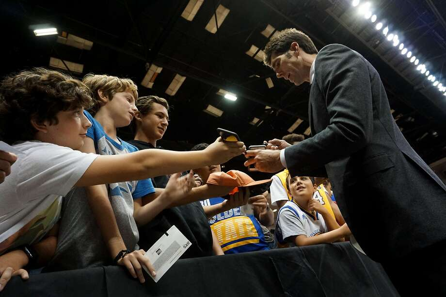 Warriors general manager Bob Myers signs autographs for fans before a game against the Los Angeles Lakers at the Valley View Casino Center in San Diego on Oct. 19. Photo: Sandy Huffaker, Special To The Chronicle