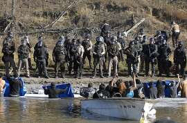 Dakota Access Pipeline protesters stand waist deep in the Cantapeta Creek, northeast of the Oceti Sakowin Camp, near Cannon Ball, N.D., Wednesday, Nov. 2, 2016. Officers in riot gear clashed again Wednesday with protesters near the Dakota Access pipeline, hitting dozens with pepper spray as they waded through waist-deep water in an attempt to reach property owned by the pipeline's developer. (Mike Mccleary/The Bismarck Tribune via AP)