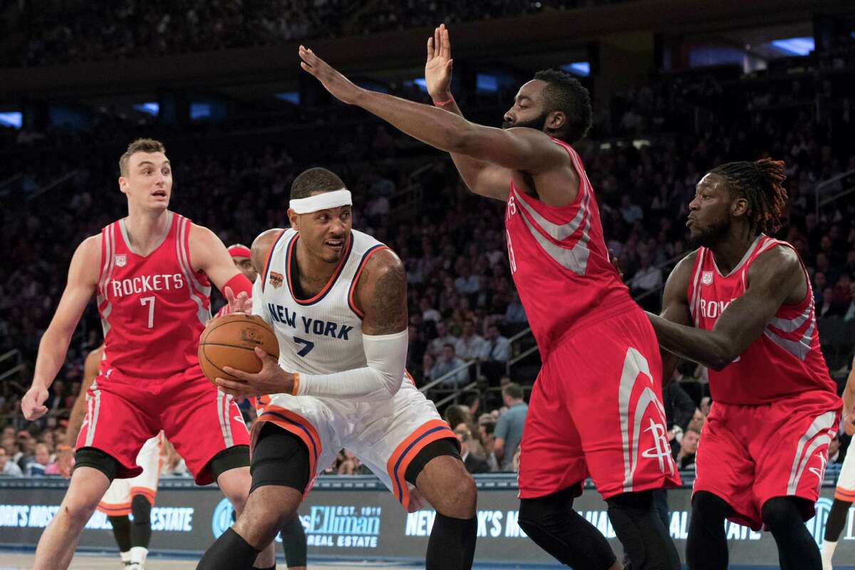 New York Knicks forward Carmelo Anthony (7) drives to the basket against Houston Rockets forward Sam Dekker, left, guard James Harden, second from right, and forward Montrezl Harrell during the second half of an NBA basketball game, Wednesday, Nov. 2, 2016, at Madison Square Garden in New York. The Rockets won 118-99. (AP Photo/Mary Altaffer)