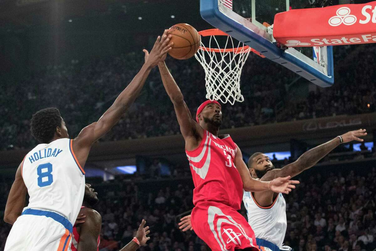 Corey Brewer, center, gets to the basket between the Knicks' Justin Holiday and Brandon Jennings.