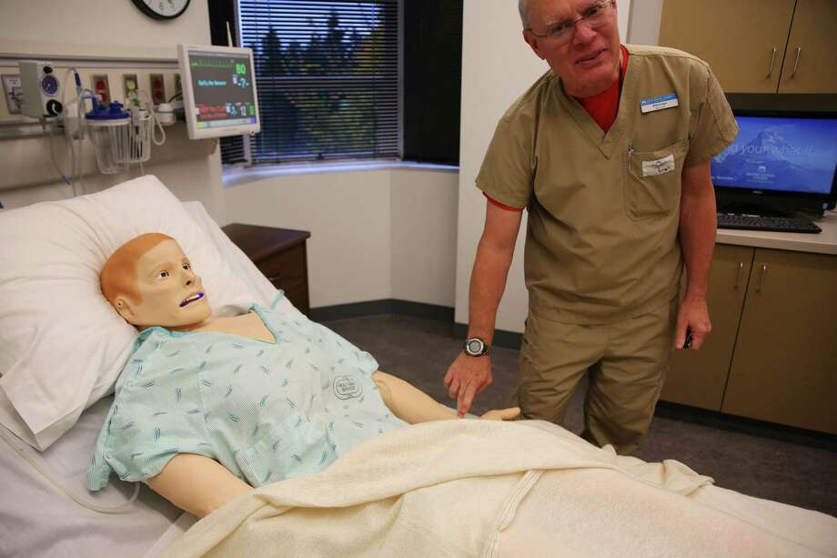Lab tech Mike Koegel checks the pulse of a $90,000 Simman 3G simulation mannequin at Seattle Central College's new Health Education center in the newly renovated Pacific Tower, Wednesday, Nov. 2, 2016.  The Simman can speak, sweat, blink, cough, simulate a seizure and other illnesses and disorders for students to diagnose. Pacific Tower held a dedication ceremony and open house, showing off the $54 million project, Wednesday evening. Photo: GENNA MARTIN, SEATTLEPI.COM / SEATTLEPI.COM