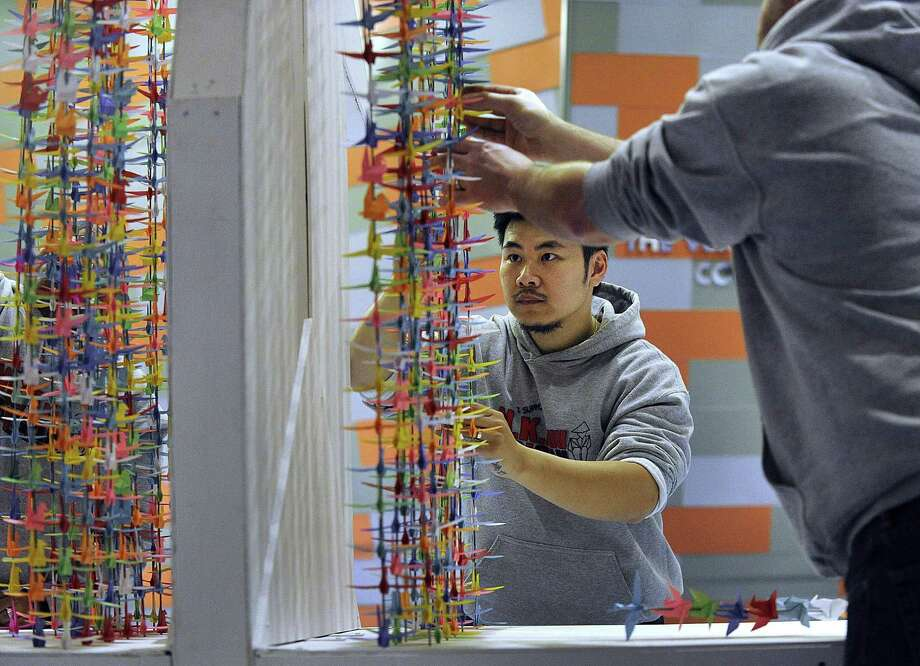 """Nghiep Luu, 29, center, assembles """"My Wish to You,"""" an origami art exhibit made of of 10,000 cranes, Wednesday, Nov. 2, 2016. Photo: Carol Kaliff / Hearst Connecticut Media / The News-Times"""