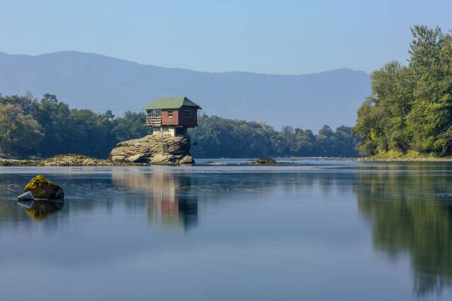 "In an undated photo, a house sits perched atop a rock in the middle of the Drina River near the town of Bajina Bašta, Serbia. China Network Television reported the house was built in 1969. In 2012, the home experienced a surge in popularity after National Geographic chose to spotlight the home in their ""Photo of the Day"" series on Aug. 2, 2012. Photo: Junlongyang, Getty Images"