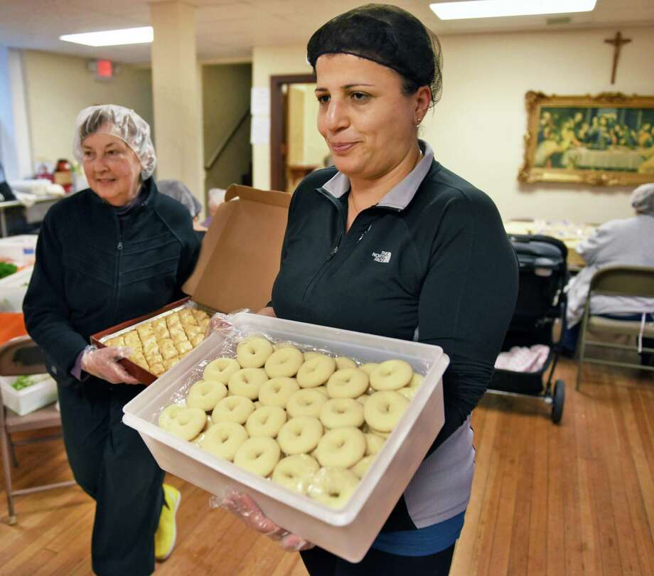 Marion Fotache, left, of Watervliet and Rita Frangieh of Latham carry in trays of Baklava and Ghreibeh as St. Ann's Maronite Catholic community prepares foods for the Hafli, an annual party in Lebanese tradition dating back centuries, on Thursday Nov. 3, 2016, at St. Ann Maronite Catholic Church in Watervliet, N.Y.  (John Carl D'Annibale / Times Union) Photo: John Carl D'Annibale / 20038630A
