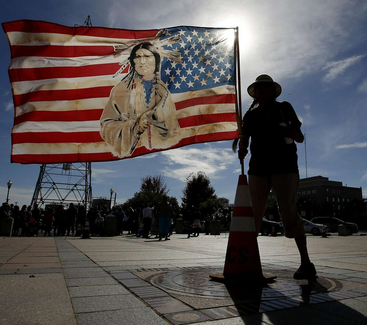 Jennell Downs, with the Kickapoo Tribe of Oklahoma, puts up a flag at the State Capitol in Oklahoma City during a protest against the Dakota Access Pipeline, Monday Oct. 31, 2016. (Steve Gooch/The Oklahoman Via AP)