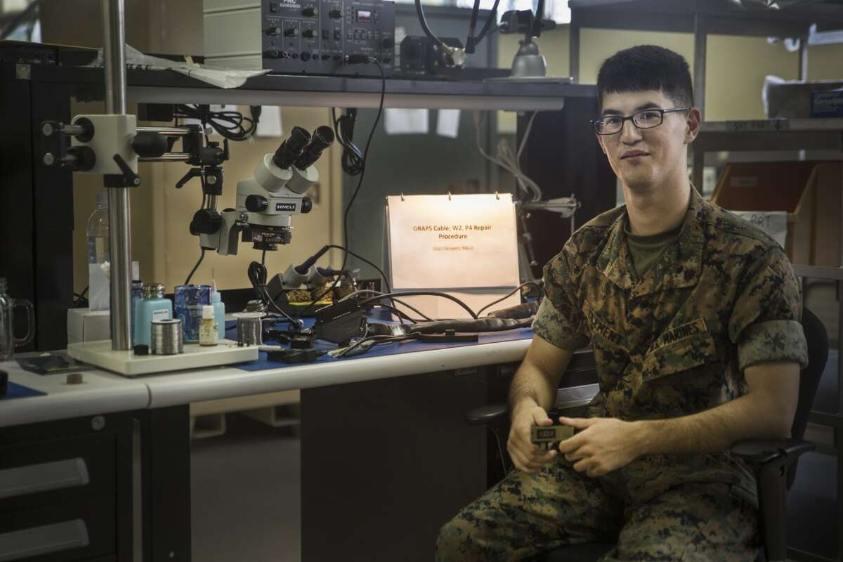 Cpl. Riki D. Clement, a micro/miniature repair man with Electronic Maintenance Company, 3rd Maintenance Battalion, Combat Logistics Regiment 35, III Marine Expeditionary Force, experiments with unused parts to fix broken radio equipment in Okinawa, Japan, Oct. 20, 2016. Clement used paper clips to replace prongs to a radio adapter presenting the potential to save the Marine Corps thousands of dollars on gear maintenance.