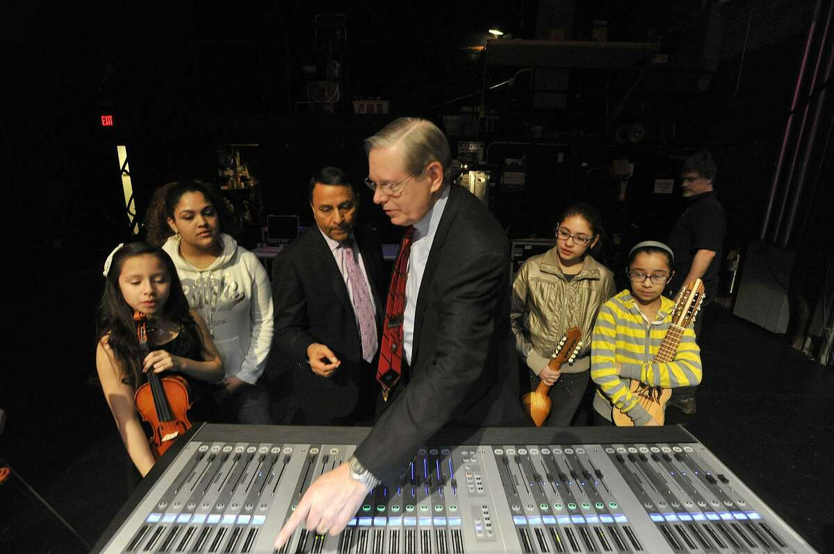 Harman Chairman, President and CEO Dinesh Paliwal shows Stamford Mayor David Martin a digital mixing board as they are flanked by INTAKE music students during the INTAKE organization's education session with people from audio equipment manufacturer Harman at the Palace Theatre in Stamford, Conn., on Monday, March 16, 2015. The students played their instruments while getting a taste of using top-of-the-line audio recording equipment.
