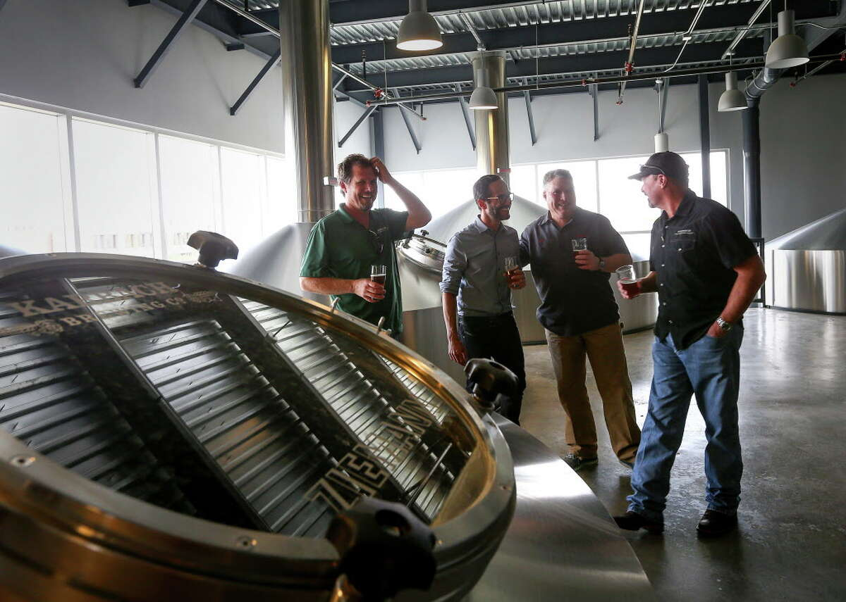 Eric Warner, brewmaster at Karbach Brewing Co., from left, Felipe Szpigel, president of Anheuser-BuschInBez's High End business unit, and Ken Goodman and Chuck Robertson, both co-founders of Karbach Brewing Co., laugh as they stand in the brewhouse at Karbach brewery, Thursday, Nov. 3, 2016, in Houston. Anheuser-Busch announced that they will acquire the company.