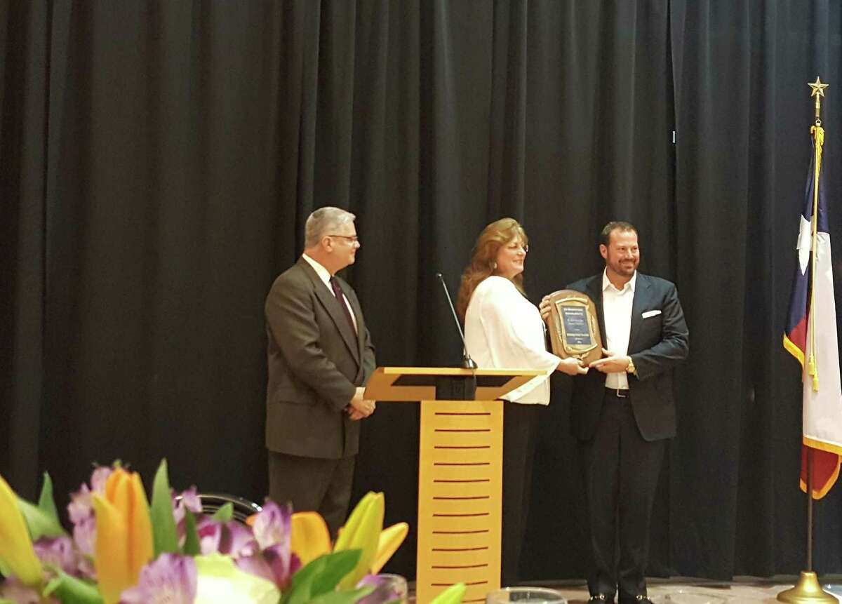 Frank McCrady (left), East Montgomery County Improvement District president, and Brenda Webb (middle), EMCSF Chair, present a plaque to Danny Signorelli (right), CEO of The Signorelli Company, during the East Montgomery County Scholarship Foundation Gala held at the East Montgomery County Improvement District Complex in New Caney Tuesday, Nov. 1.