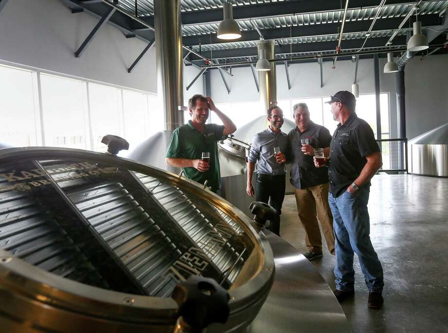 Eric Warner, brewmaster at Karbach Brewing Co., from left, Felipe Szpigel, president of Anheuser-BuschInBez's High End business unit, and Ken Goodman and Chuck Robertson, both co-founders of Karbach Brewing Co., laugh as they stand in the brewhouse at Karbach brewery, Thursday, Nov. 3, 2016, in Houston. Photo: Jon Shapley, Staff / © 2015  Houston Chronicle