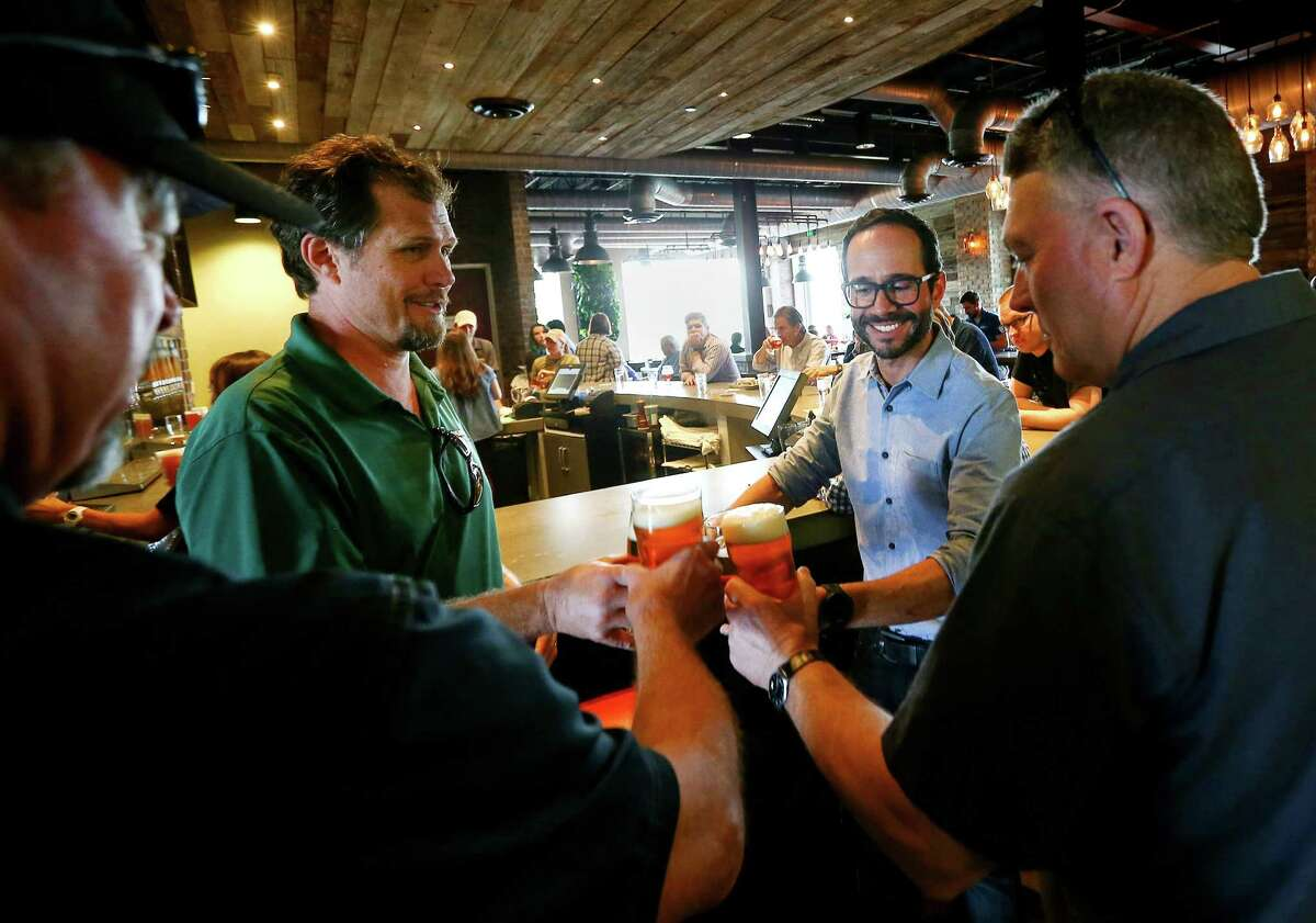 Karbach co-founder Chuck Robertson, left, toasts the deal with Eric Warner, Karbach brewmaster; Felipe Szpigel of Anheuser-BuschInBev; and Karbach co-founder Ken Goodman.