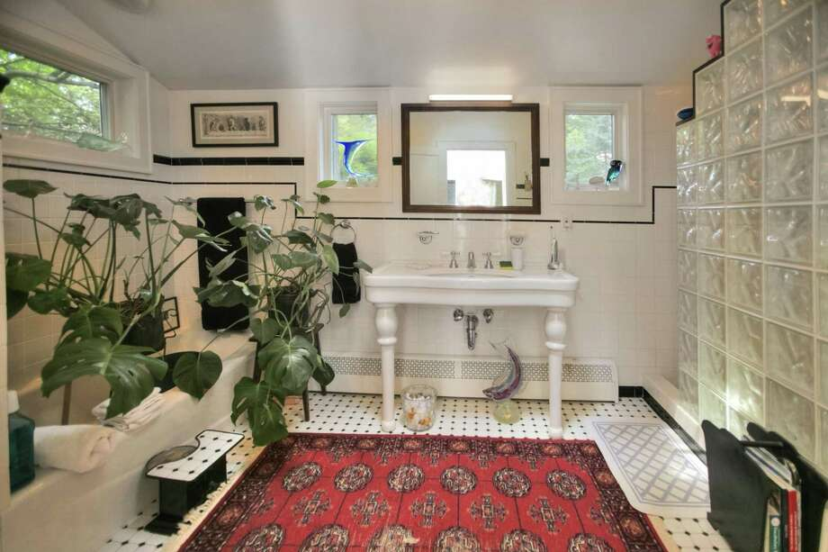 The good size bath features a wall of 1950s-style glass cubes, soaking tub, skylight, a ceramic tile floor and white ceramic tiles on the walls with a border of thin black tiles to match the floor.