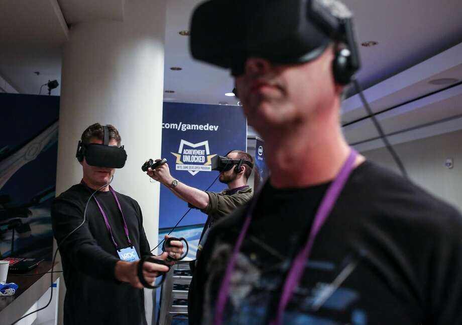 (Front to back) Brett Branch, Jason Schugardt, and JMatthew Noyas throw and block fireballs as they try out a VR system running on Intel Corei7 at the Virtual Reality Developers Conference on Thursday, Oct 3, 2016 in San Francisco, Calif. Photo: Amy Osborne, Special To The Chronicle