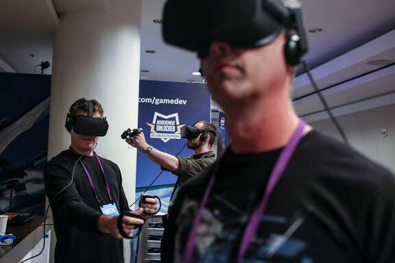 (Front to back) Brett Branch, Jason Schugardt, and JMatthew Noyas throw and block fireballs as they try out a VR system running on Intel Corei7 at the Virtual Reality Developers Conference on Thursday, Oct 3, 2016 in San Francisco, Calif.