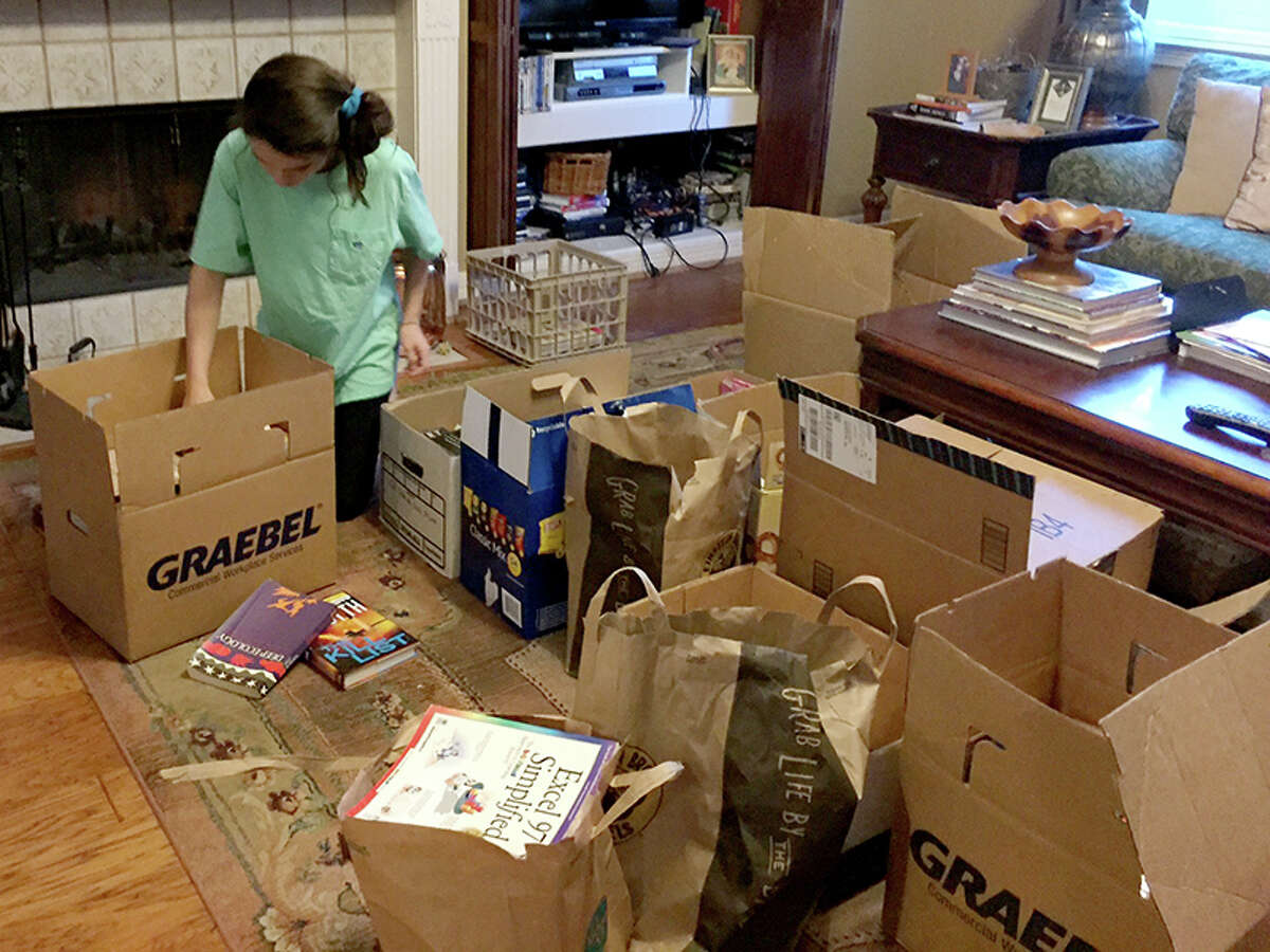 Juliana Oyen gathers up and sorts all of the donated books into boxes to be shipped to Baton Rouge.