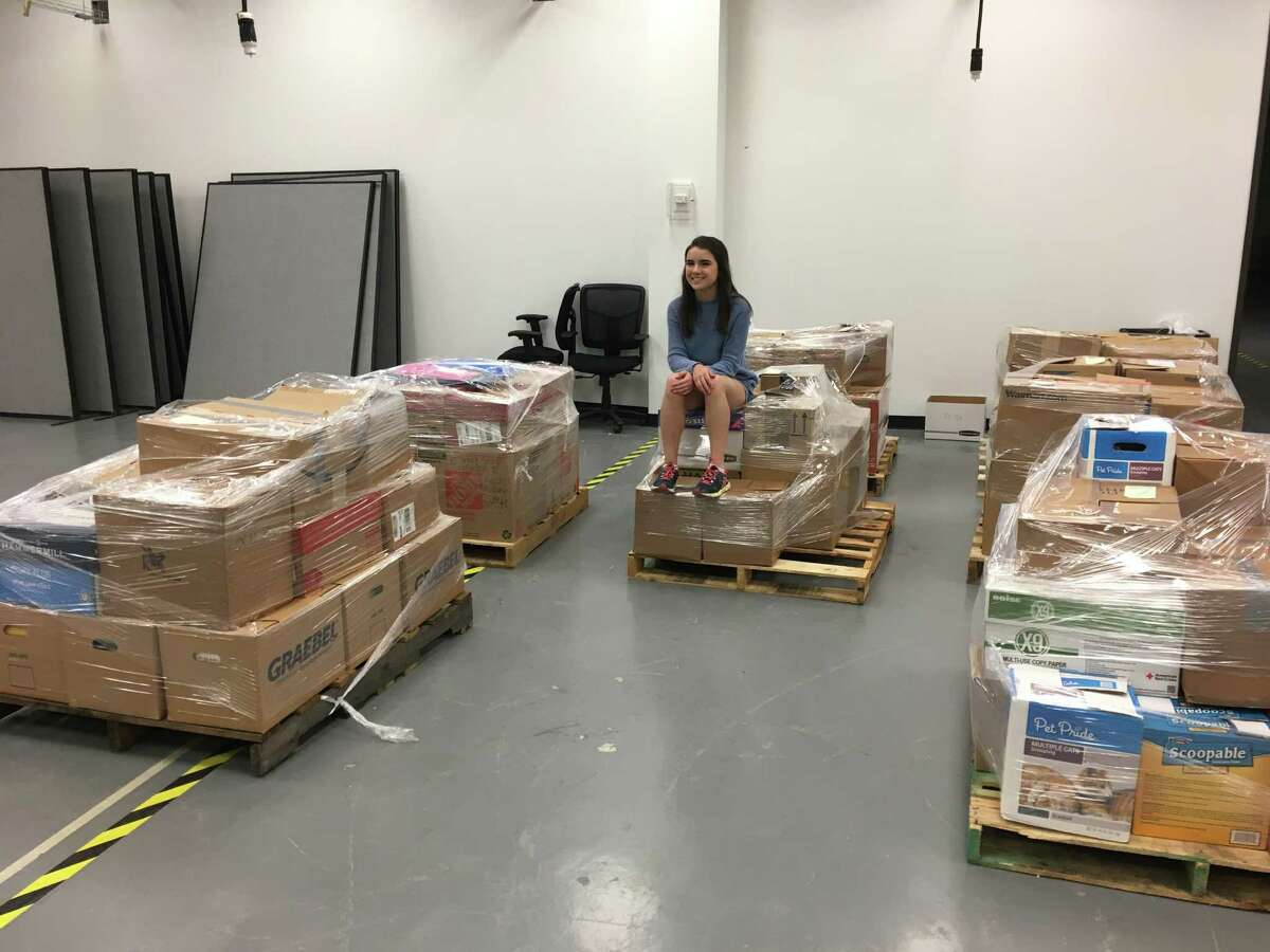 Juliana Oyen sits with the donated books that are ready to be shipped to Baton Rouge.