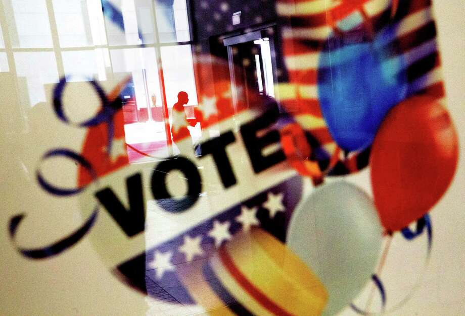 A voter is reflected in the glass frame of a poster while leaving a polling site during early voting ahead of next week's election in Atlanta, Tuesday, Nov. 1, 2016. Early voting, via mail or in-person, is underway in 37 states. In all, more than 46 million people, or as much as 40 percent of the electorate, are expected to vote before Election Day, Nov. 8. (AP Photo/David Goldman) ORG XMIT: GADG101 Photo: David Goldman / Copyright 2016 The Associated Press. All rights reserved.