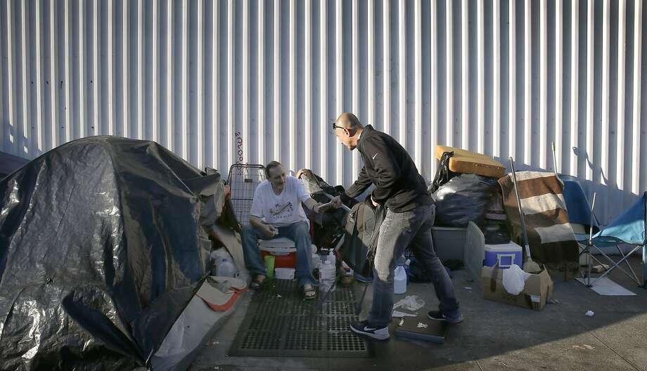 Outreach specialist Dennis Johnson distributes rain ponchos while seeking veterans living in S.F. homeless encampments. Photo: Paul Chinn, The Chronicle