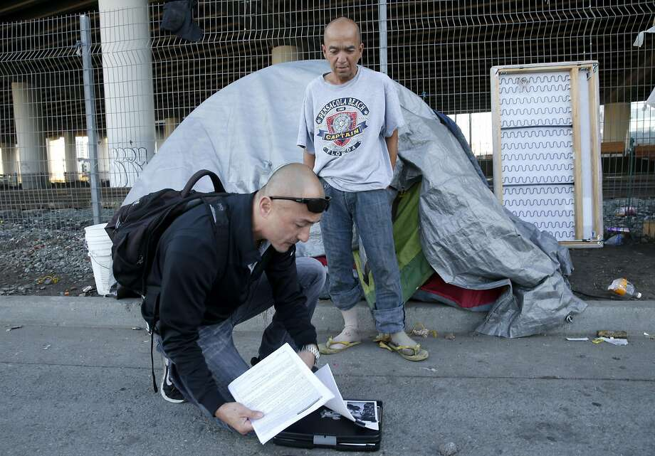 Outreach specialist Dennis Johnson signs up Army veteran Enrico Cruz (top) for homeless veterans services in San Francisco. Photo: Paul Chinn, The Chronicle