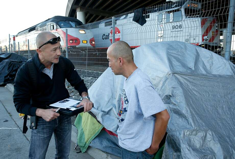 Dennis Johnson, an outreach specialist with Swords to Plowshares, enrolls Army veteran Enrico Cruz (right) in services for homeless veterans. Cruz and other S.F. homeless live in an encampment on Seventh Street next to the Caltrain tracks. Photo: Paul Chinn, The Chronicle