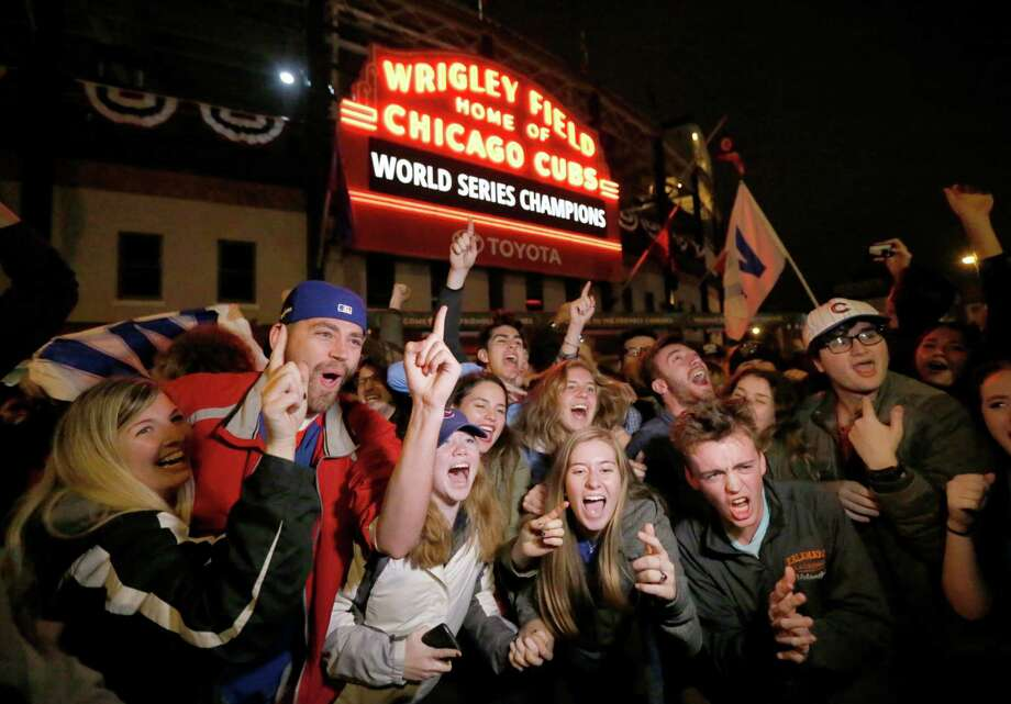 Chicago Cubs fans celebrate in front of Wrigley Field in Chicago on Wednesday, Nov. 2, 2016, after the Cubs defeated the Cleveland Indians 8-7 in Game 7 of the baseball World Series in Cleveland. (AP Photo/Charles Rex Arbogast) Photo: Charles Rex Arbogast, STF / Copyright 2016 The Associated Press. All rights reserved.